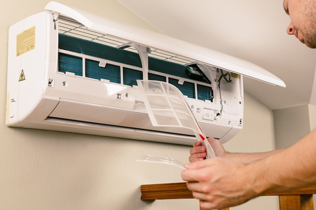 Male technician cleaning air conditioner indoors Premium Photo