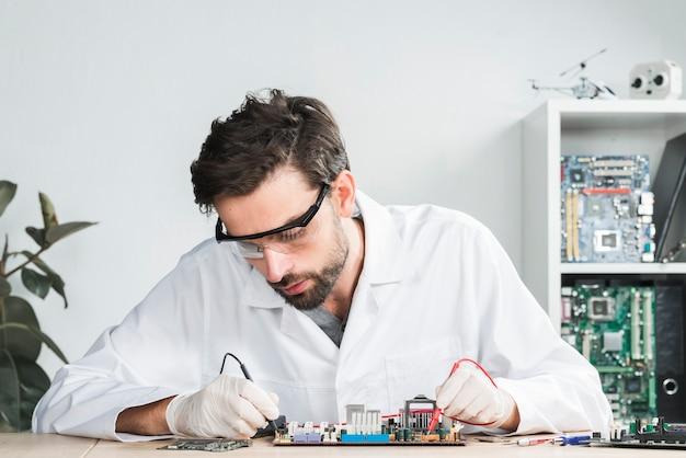 Male technician examining broken computer with digital multimeter Free Photo