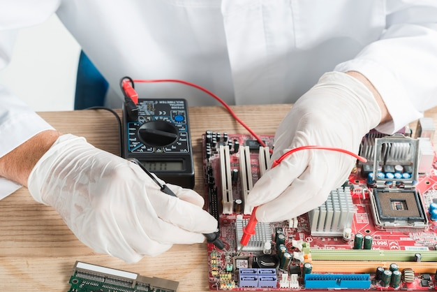 Male technician examining computer motherboard with digital multimeter Free Photo