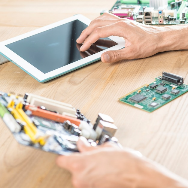 Male technician hand touching digital tablet holding motherboard on wooden table Free Photo