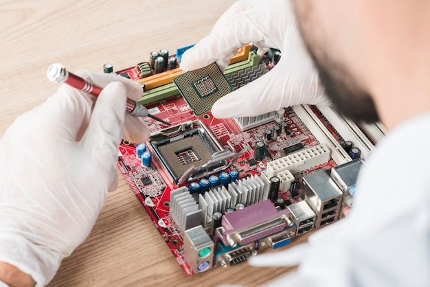 Male technician inserting chip in computer motherboard on wooden desk Free Photo