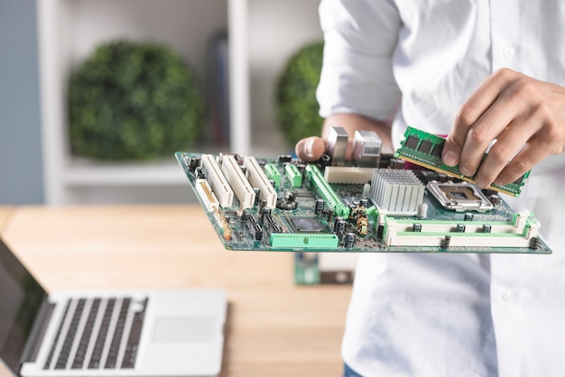Male technician inserting ram in modern pc computer motherboard Premium Photo