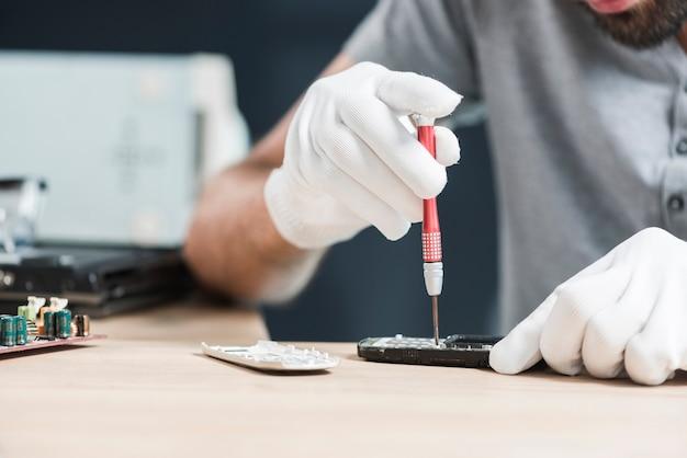 Male technician repairing cellphone over wooden desk Free Photo