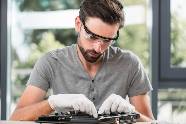 Male technician in safety glasses repairing computer Free Photo