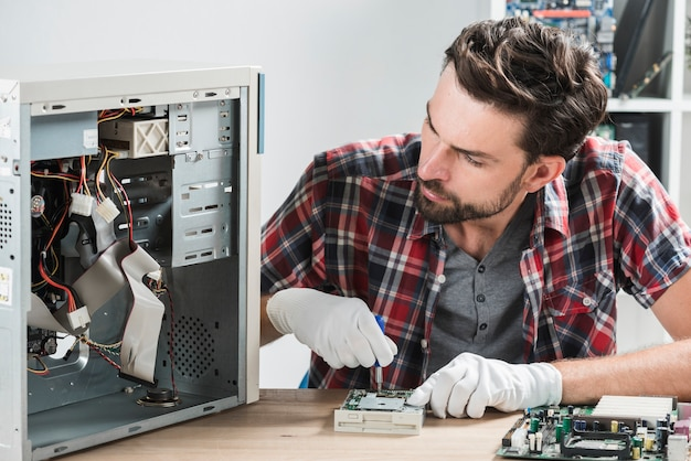 Male technician working on broken computer Free Photo