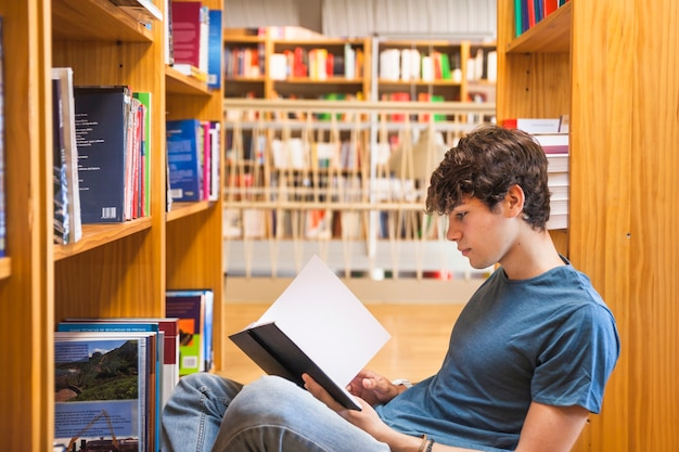 Male teenager leaning on bookcase and reading Free Photo