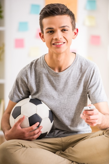 Male teenager sitting at home and holding soccer ball. Premium Photo