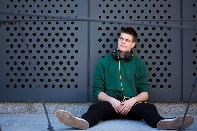 Male teenager with headphones sitting on floor and leaning back with spread legs Free Photo