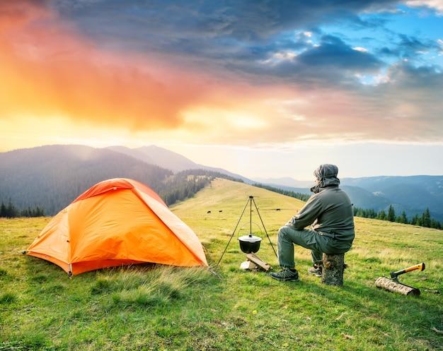 Мужчина-турист сидит на бревне возле оранжевой палатки в горах Premium Фотографии