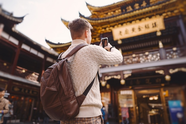 Male tourist taking photos of a pagoda at yuyuan market in shanghai Free Photo