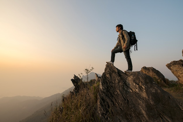 Male tourist on top of gray mountain in fog in autumn Premium Photo