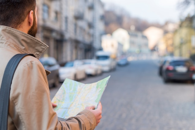 A male traveler holding map in hand finding the way on city street Free Photo