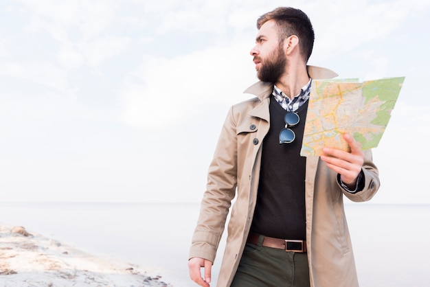 Male traveler standing on beach holding map in hand looking away Free Photo
