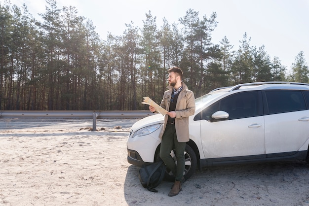 Male traveler standing near his luxurious car holding map in hand looking away Free Photo