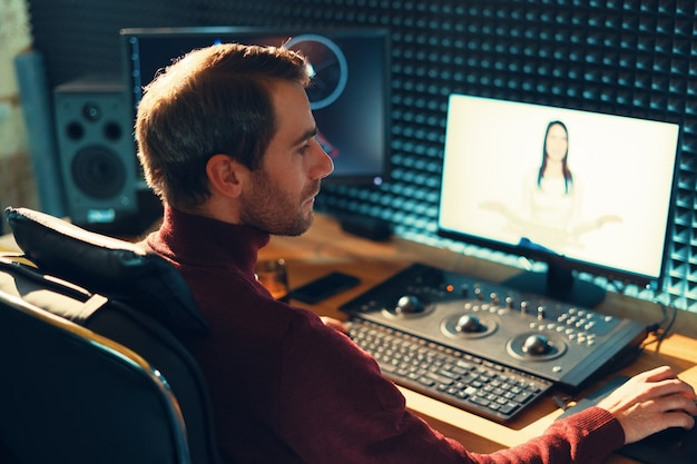 Мужчина-видеооператор редактирует и обрезает кадры и звук на своем персональном компьютере Premium Фотографии