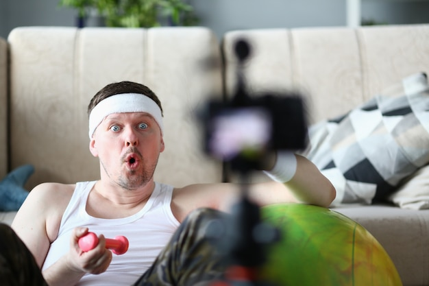 Male vlogger holds dumbbells in his Premium Photo
