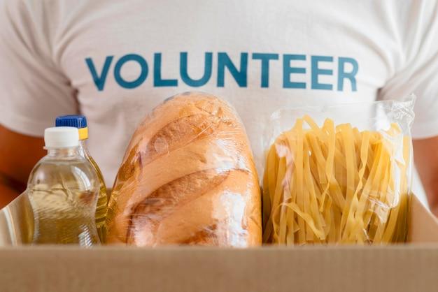Мужской волонтер держит коробку с продуктами для благотворительности Бесплатные Фотографии