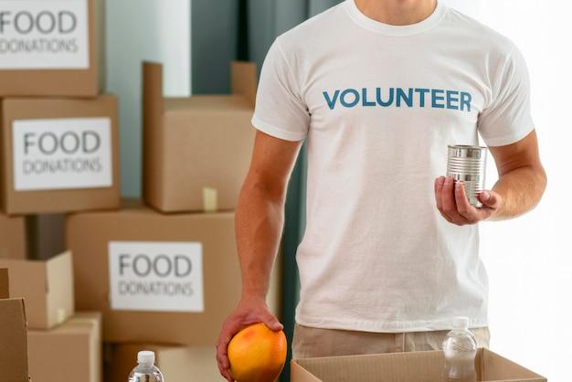 Мужчина-волонтер готовит еду для пожертвования на благотворительность Бесплатные Фотографии