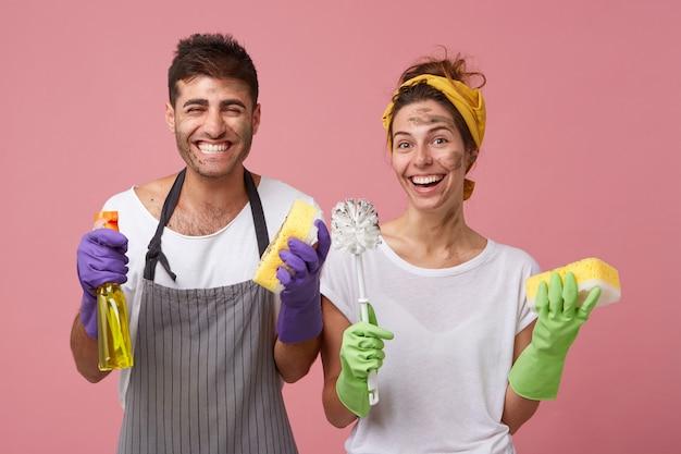 Grembiule da portare maschio e femmina in maglietta bianca che sorride ampiamente essendo felice di pulire Foto Gratuite