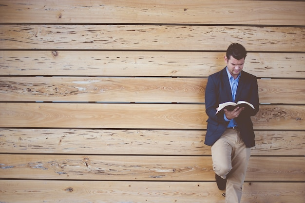 Male wearing a suit leaning against the wall while reading the bible Free Photo