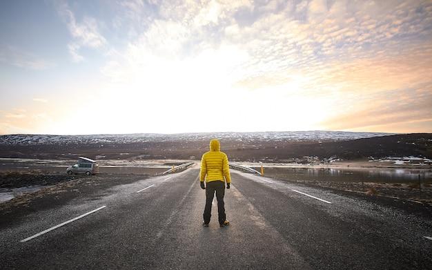 Uomo che indossa una giacca gialla mentre si trova nel mezzo di una strada deserta guardando in lontananza Foto Gratuite