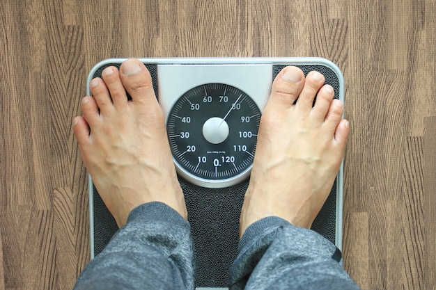Male on the weight scale for check weight, diet concept Premium Photo