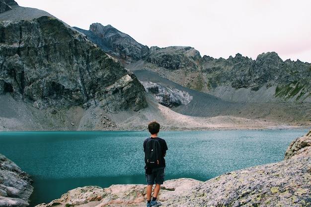 山の近くの海の景色を楽しみながら崖の上に立っているバックパックを持つ男性 無料写真