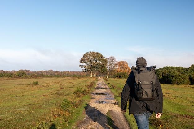 Maschio con uno zaino che cammina attraverso un sentiero in un campo Foto Gratuite