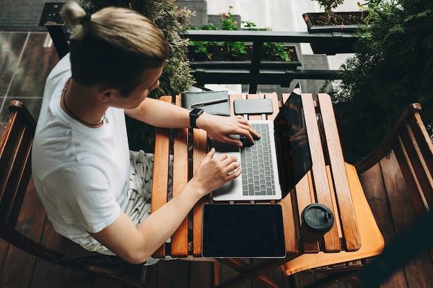 나무 판자 카페 테이블에 캐주얼 한 여름 옷에 앉아있는 창조적 인 머리를 가진 남성 프리미엄 사진