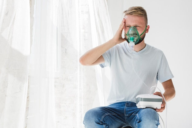 Male with nebulizer holding head Free Photo