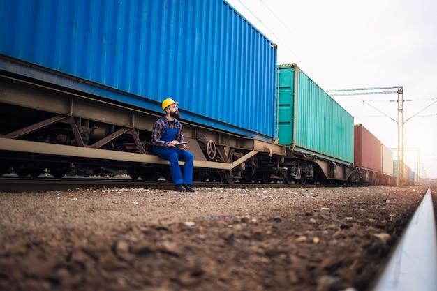 Lavoratore di sesso maschile che controlla i rimorchi del treno con i container prima della partenza Foto Gratuite