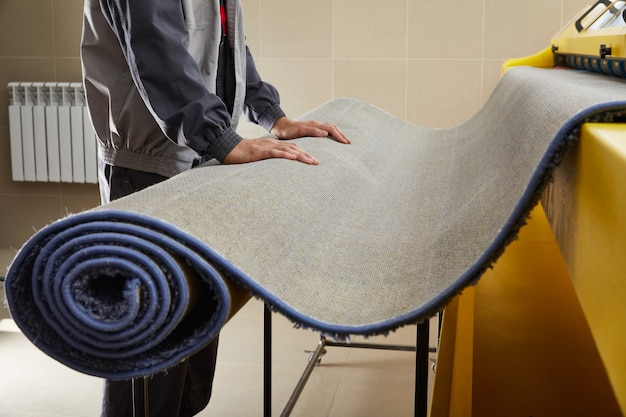 Male worker cleaning carpet on automatic washing machine equipment and dryer in the laundry room Premium Photo