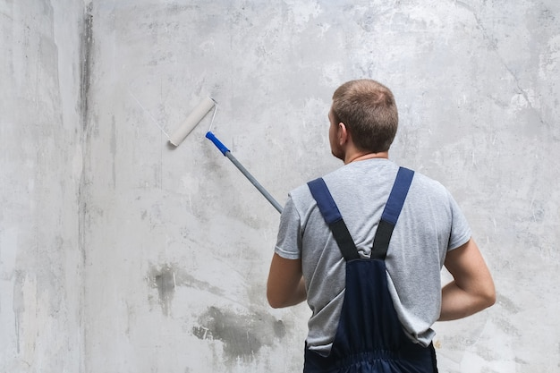 A male worker primes the wall with a roller for better grip. Premium Photo