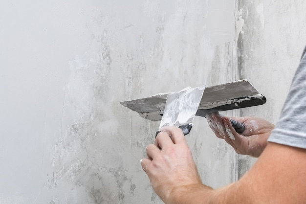 A male worker spreads the putty mixture and flattens the wall. Premium Photo