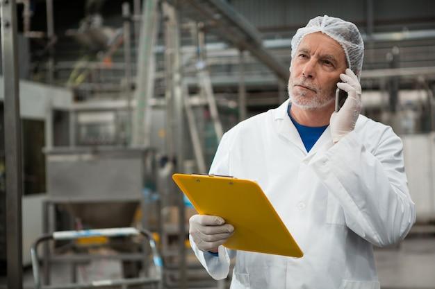 Мужчина-работник разговаривает по мобильному телефону на заводе холодных напитков Бесплатные Фотографии