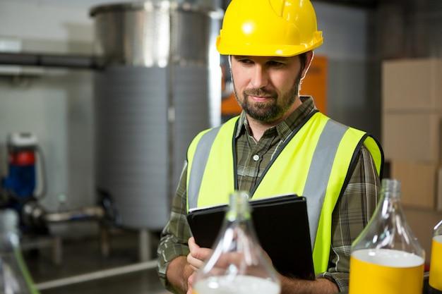 工場でデジタルタブレットを使用している男性労働者 無料写真