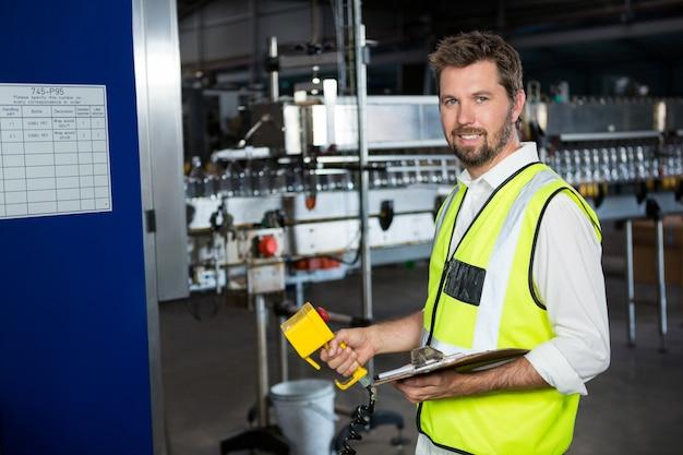 ジュース工場で機械を使用している男性労働者 無料写真