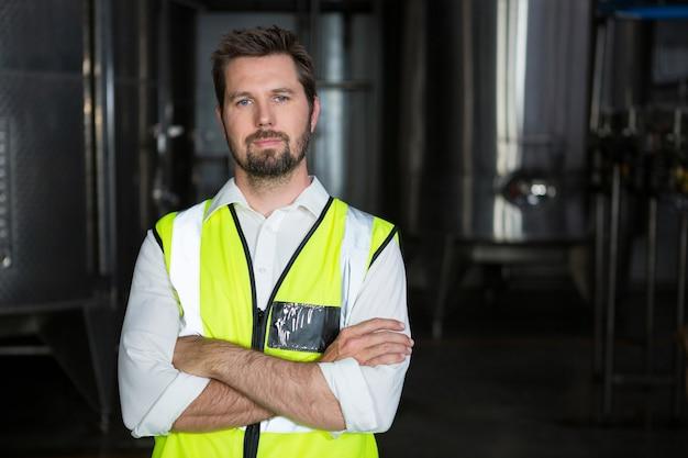 工場で腕を組んで立っている男性労働者 無料写真