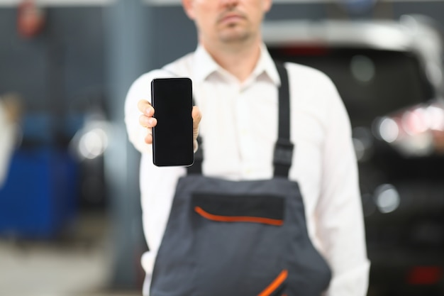 Male in working clothes showing gadget Premium Photo