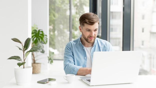 Мужчина работает на ноутбуке Premium Фотографии