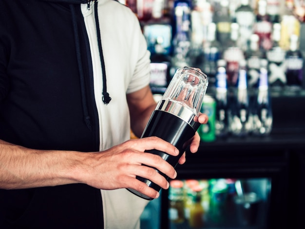 Male young bartender using tumbler to make drink Free Photo