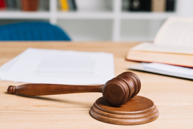 Mallet on gavel over wooden table in courtroom Premium Photo