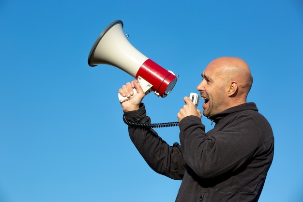 Man acivist demonstartor shouting, screaming to the megaphone during huge demonstration event, economic crisis, unemployment Premium Photo