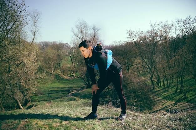Человек после бега в парке или лесу на фоне деревьев Бесплатные Фотографии