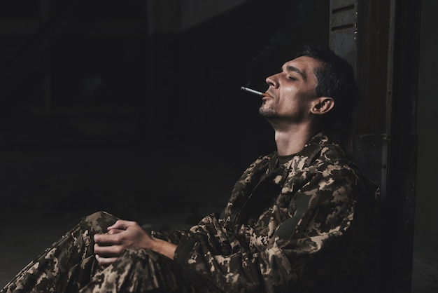 Man after the war smokes and depressed. Premium Photo