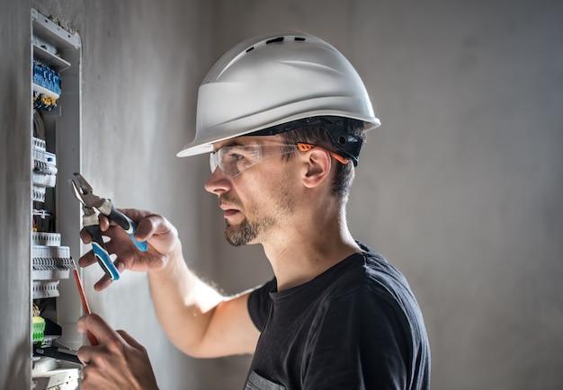 ヒューズ付き配電盤で働く電気技術者の男性。電気機器の設置と接続。 無料写真