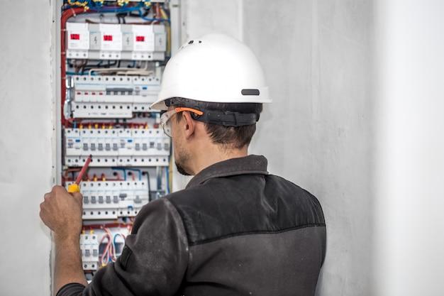 Человек, электротехник, работает в распределительном щите с предохранителями. установка и подключение электрооборудования. Бесплатные Фотографии