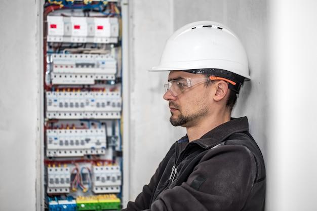 Мужчина, электрик работает в распределительном щите с предохранителями. монтаж и подключение электрооборудования. Бесплатные Фотографии