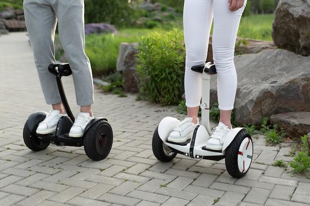 男と女が公園で電動スクーターを運転 Premium写真