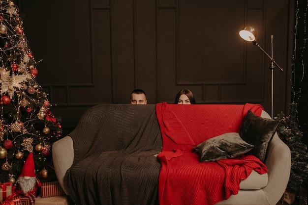 Мужчина и женщина спрятались за диваном. из-за дивана торчат головы мужчины и женщины. Premium Фотографии